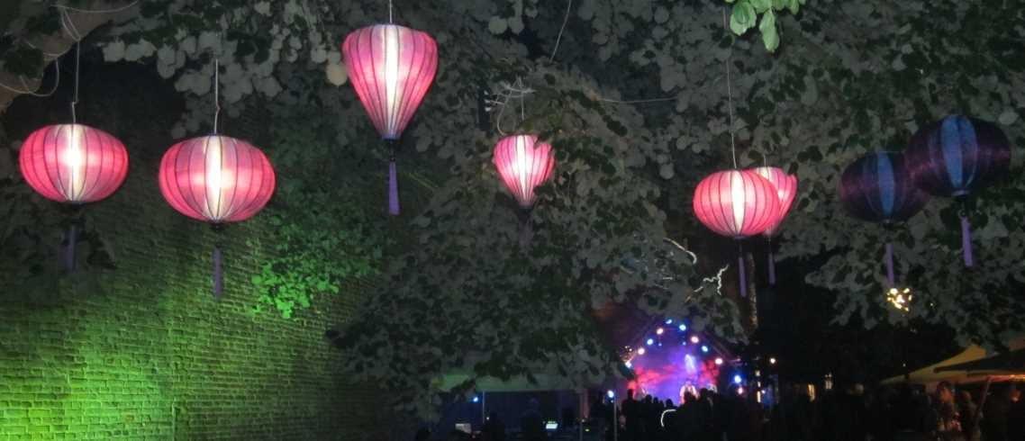 Lilafarbene Lampions in Bäume gehängt auf einem Gartenfest