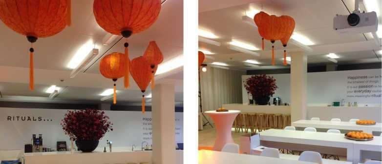 Oranje Vietnamese lampions aan het plafond die de beursstand van Rituals decoreren