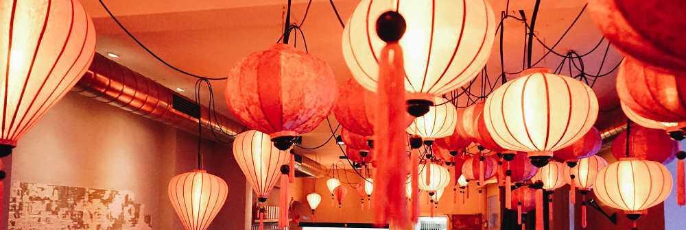 Een verzameling roze lampions als hanglamp aan het plafond van een Vietnamees restaurant