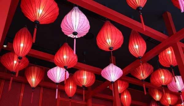 Eine Mischung aus roten und rosafarbenen Lampions an der Decke eines Restaurants.